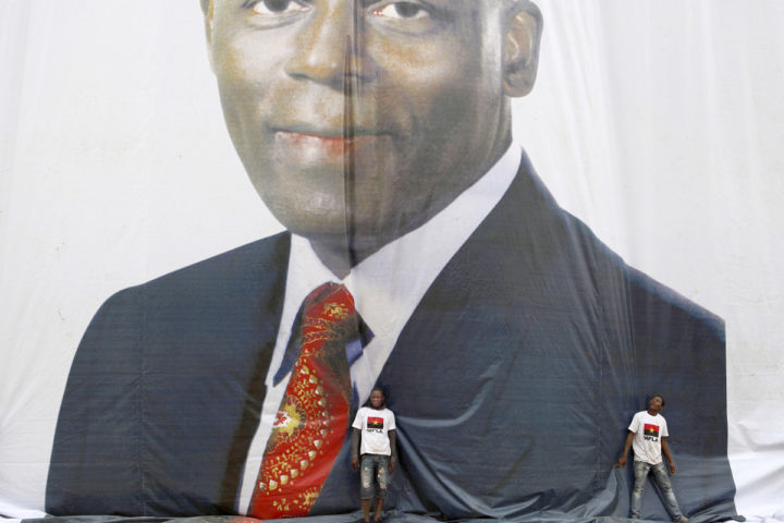 MPLA (People's Movement for the Liberation of Angola) supporters stop a banner of President Jose Eduardo Dos Santos from blowing away during a rally in Luanda, ahead of the parliamentary elections.