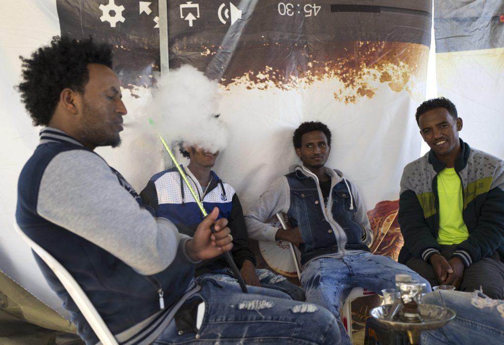 2015-12-02 13:57:11 epa05052095 African migrants smoke water pipes or 'Shisha' in a cafe outside the Holot detention center in the Negev Desert, in Israel, along the Egyptian border, 02 December 2015. Israel media reports that the center is the fullest it has ever been, housing some 2,500 asylum seekers mainly from Eritrea and Sudan. Hundreds more are expected to be sent there by Israeli authorities in the coming weeks. The detention center allows prisoners to be outside, but they must report back several times and be back for the night, and cannot work. EPA/JIM HOLLANDER