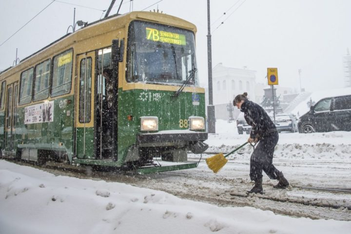 2016-11-09 16:56:04 epa05624374 A tram driver cleans the switch to get to the right track in the Senate square in Helsinki, Finland, 09 November 2016. Due to easterly winds and open sea, it has been snowing for three days on the southern coast of Finland causing difficulties for the traffic. EPA/MARKKU OJALA FINLAND OUT