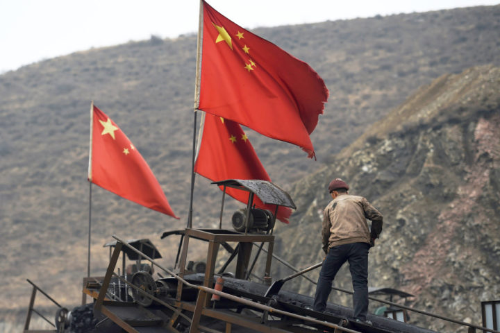 2015-11-20 10:53:21 TO GO WITH China-economy-environment-coal-climate,FOCUS by Tom HANCOCK In this photo taken on November 20, 2015, Chinese flags fly as a worker clearing a conveyer belt used to transport coal, near a coal mine at Datong, in China's northern Shanxi province. For decades coal has been the backbone of the northern province of Shanxi, providing livelihoods for millions of miners, while private jet owning bosses became notorious for their nouveau riche lifestyles. AFP PHOTO / GREG BAKER