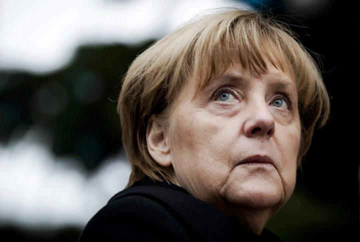 2016-12-20 14:58:32 BERLIJN - Bondskanselier Angela Merkel bekijkt de bloemenzee in de buurt van de plek waar een vrachtwagen inreed op een kerstmarkt in Berlijn. ANP REMKO DE WAAL