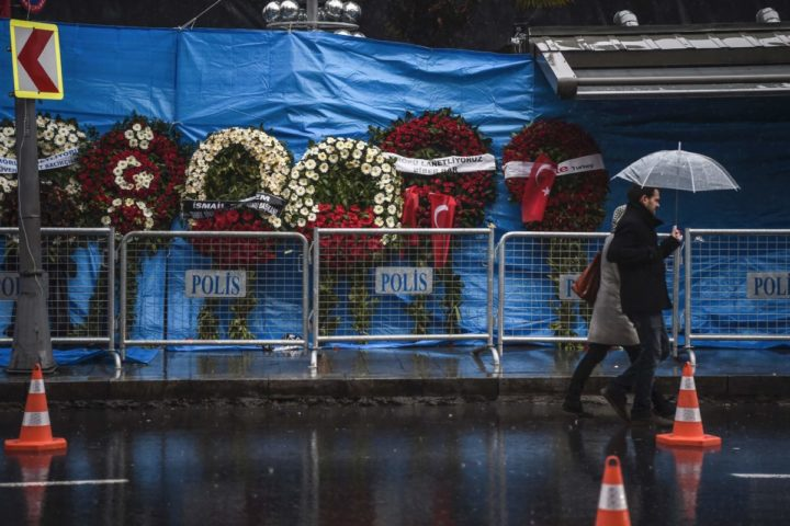 2017-01-05 11:42:39 A couple walk past the Reina nightclub on January 5, 2017 in Istanbul, days after a gunman killed 39 people on New Year's night. The gunman who killed 39 people at an Istanbul nightclub had fought in Syria for Islamic State jihadists, a report said on January 3, as Turkish authorities intensified their hunt for the attacker. Of the 39 dead, 27 were foreigners, mainly from Arab countries, with coffins repatriated overnight to countries including Lebanon and Saudi Arabia. / AFP PHOTO / OZAN KOSE