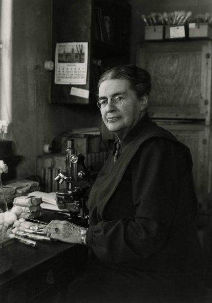 Johanna Westerdijk met kweekbuisjes en een microscoop. Deze foto is rond 1948 genomen.