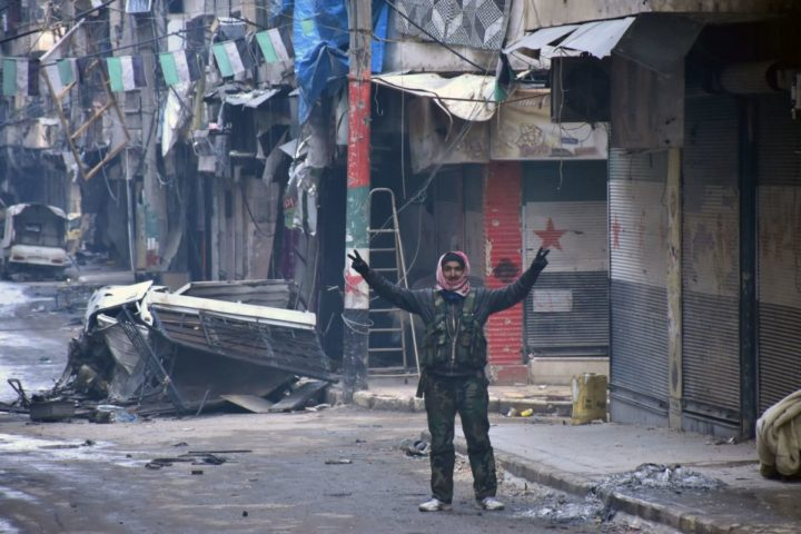 2016-12-23 14:22:11 TOPSHOT - A Syrian man gestures in the former rebel-held Salaheddin district in the northern Syrian city of Aleppo on December 23, 2016 after Syrian government forces retook control of the whole embattled city. Syrian troops cemented their hold on Aleppo after retaking full control of the city, as residents anxious to return to their homes moved through its ruined streets.  / AFP PHOTO / George OURFALIAN