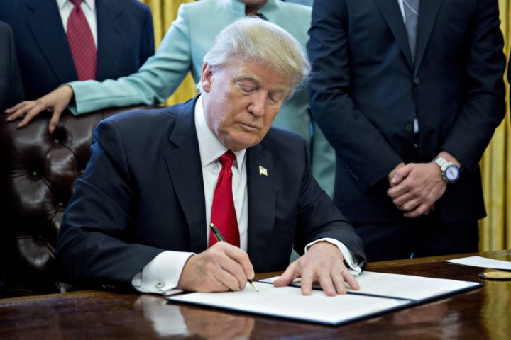 2017-01-30 10:07:10 epa05761659 US President Donald J. Trump signs an executive order, while surrounded by small business leaders in the Oval Office of the White House in Washington, DC, USA, 30 January 2017. Trump said the executive order will 'dramatically' reduce regulations on small businesses. EPA/ANDREW HARRER / POOL