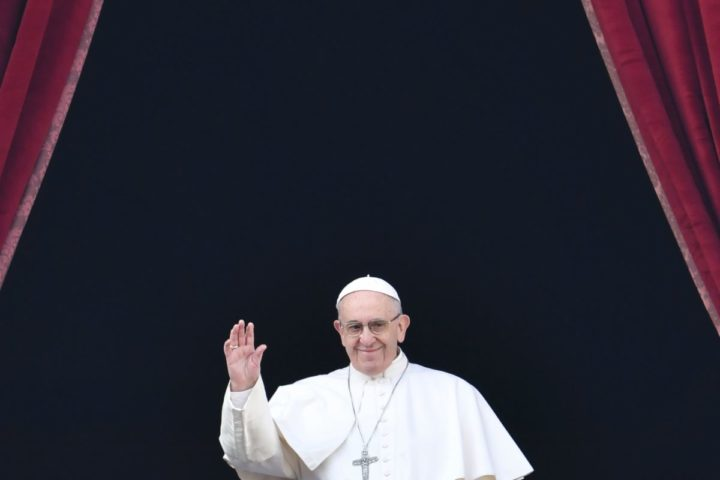 "2016-12-25 12:00:16 Pope Francis waves from the balcony of St Peter's basilica during the traditional ""Urbi et Orbi"" Christmas message to the city and the world, on December 25, 2016 at St Peter's square in Vatican. / AFP PHOTO / ANDREAS SOLARO"