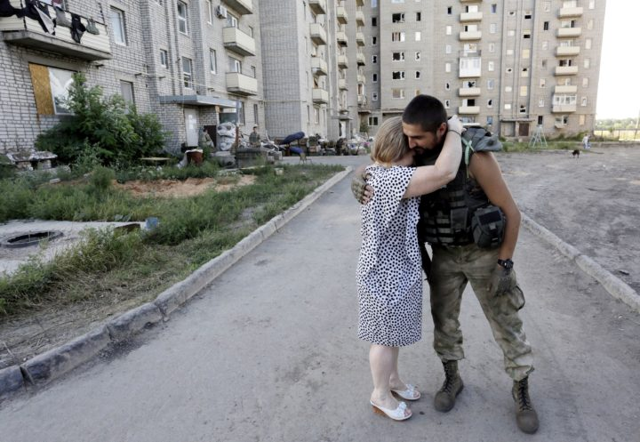 2015-08-24 09:27:32 A woman embraces an Ukrainian serviceman near Avdiivka, Donetsk region on August 24, 2015. Ukrainian President Petro Poroshenko accused Russia of this week sending three military convoys over the border into the separatist-controlled east with a total of up to 500 tanks, 400 artillery systems and up to 950 military armoured vehicles to pro-Russian rebels, although he did not specify the time period for these deliveries. AFP PHOTO/ ANATOLII STEPANOV