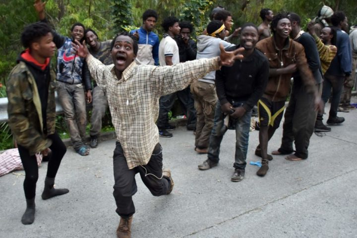 2017-02-17 07:16:54 TOPSHOT - Migrants celebrate outside the Center for Temporary Stay of Immigrants (CETI) after forcing their way through a fence between Morocco and the tiny Spanish enclave of Ceuta on February 17, 2017. Hundreds of migrants stormed the border between Morocco and Spain at Ceuta today, days after Morocco warned the EU of fresh migrant trouble failing progress over a trade deal. / AFP PHOTO / Antonio SEMPERE