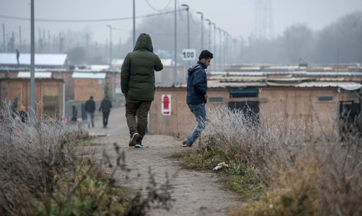 2017-01-25 12:05:51 Migrants walk inside the migrants camp of Grande-Synthe on January 25, 2017 in Grande-Synthe, northern France. / AFP PHOTO / PHILIPPE HUGUEN