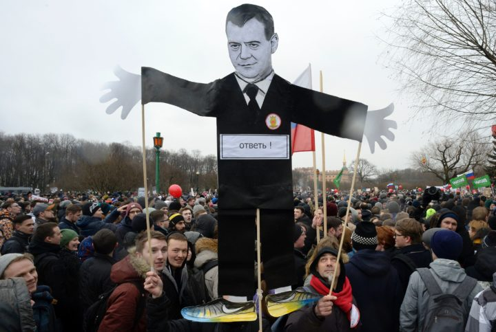 2017-03-26 13:19:36 Opposition supporters with a cutout figure depicting Prime Minister Dmitry Medvedev participate in an anti-corruption rally in central Saint Petersburg on March 26, 2017. Thousands of Russians demonstrated across the country on March 26 to protest at corruption, defying bans on rallies which were called by prominent Kremlin critic Alexei Navalny -- who was arrested along with scores of others. Navalny called for the protests after publishing a detailed report this month accusing Prime Minister Dmitry Medvedev of controlling a property empire through a shadowy network of non-profit organisations. / AFP PHOTO / Olga MALTSEVA