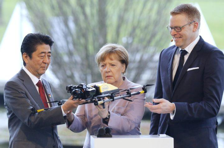 De Duitse bondskanselier Angela Merkel (midden) bekijkt een drone met de Japanse premier Shinzo Abe (R) - Foto: AFP