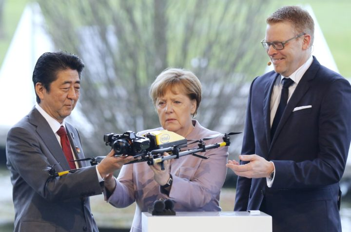 2017-03-20 11:20:14 epa05859477 German Chancellor Angela Merkel (C) and the Japanese Prime Minister Shinzo Abe (L) examine a drone at the Intel booth during their opening walkabout at the CeBIT computing trade fair in Hanover, northern Germany, 20 March 2017. Reports state that more than 3.000 exhibitors from 70 countries are showing their products and solutions at the fair which expects to see about 200.000 visitors from 20 to 24 March 2017. EPA/FOCKE STRANGMANN