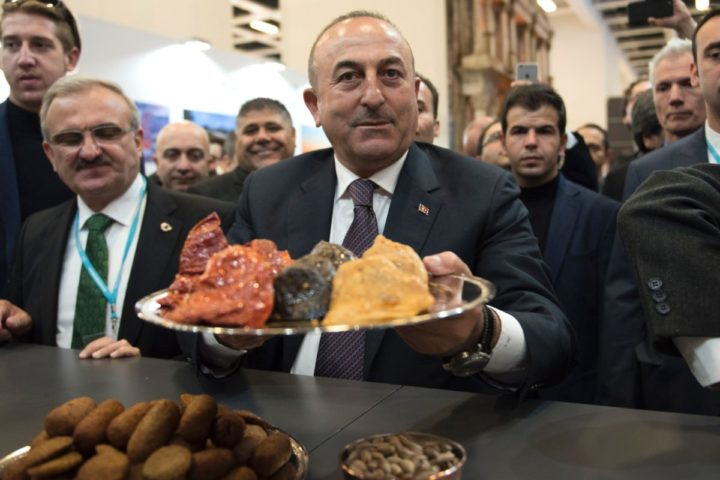 """2017-03-08 10:56:04 Turkish Foreign Minister Mevlut Cavusoglu offers Turkish culinary specialities during a visit to his country's hall at the Internationale Tourismus-Boerse (ITB) international travel trade show in Berlin on March 8, 2017. Cavusoglu said he expected to host his German counterpart Sigmar Gabriel """"as soon as possible,"""" as the NATO allies struggle to end a bad-tempered row. / AFP PHOTO / Steffi LOOS"""