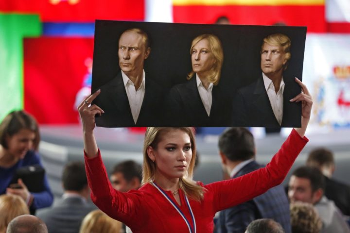 2016-12-23 13:50:51 epa05686671 A journalist holds a poster with portraits of (L-R) Russian President Vladimir Putin, France's far-right National Front president Marine Le Pen, and US President-elect Donald Trump prior Putin's annual press conference in International Trade Center in Moscow, Russia, 23 December 2016. A total of 1,437 journalist from all regions of Russia are accredited at the press conference with many of them using various creative ways to attract the attention of the Russian leader and to ask their questions. EPA/YURI KOCHETKOV