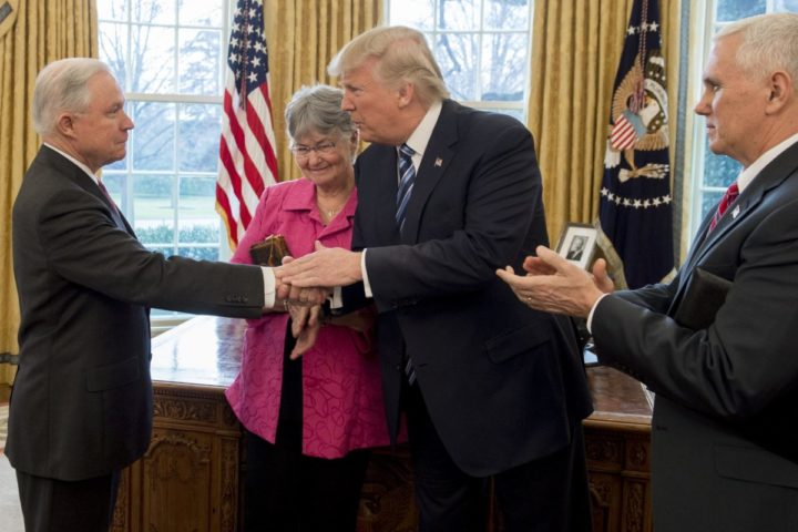 2017-02-09 11:28:11 US President Donald Trump shakes hands with Jeff Sessions (L), alongside his wife Mary (2nd L), after he was sworn in as Attorney General by US Vice President Mike Pence (R) in the Oval Office of the White House in Washington, DC, February 9, 2017. / AFP PHOTO / SAUL LOEB