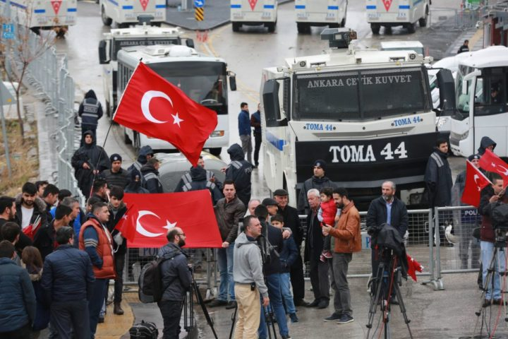 "2017-03-12 10:00:43 Turkish residents waving their na tional flag gather by a blockade of anti-riot police vehicles and a sealed off area surrounding the Dutch consulate on March 12, 2017 in Ankara, for ""security reasons"" as a crisis escalated between Turkey and The Netherlands after Turkey's Foreign minister was barred from speaking in the country to promote a referendum at home. Turkish President Recep Tayyip Erdogan on March 12 warned the Netherlands it would pay a price for preventing top ministers from holding rallies ahead of a referendum on expanding his powers, as a crisis escalated with Turkey's key EU partners. / AFP PHOTO / ADEM ALTAN"