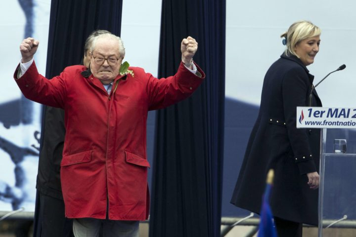 2015-05-01 09:26:57 (FILES) A file picture taken in Paris on May 1, 2015 shows France's far-right political party Front National (FN) founder and honorary president Jean-Marie Le Pen gesturing on stage as FN's president Marine Le Pen looks on during the party's annual rally in honour of Joan of Arc. The Court of Appeal of Versailles will return its verdict on July 28 concerning the status of Jean-Marie le Pen as honorary president of the FN. AFP PHOTO / KENZO TRIBOUILLARD