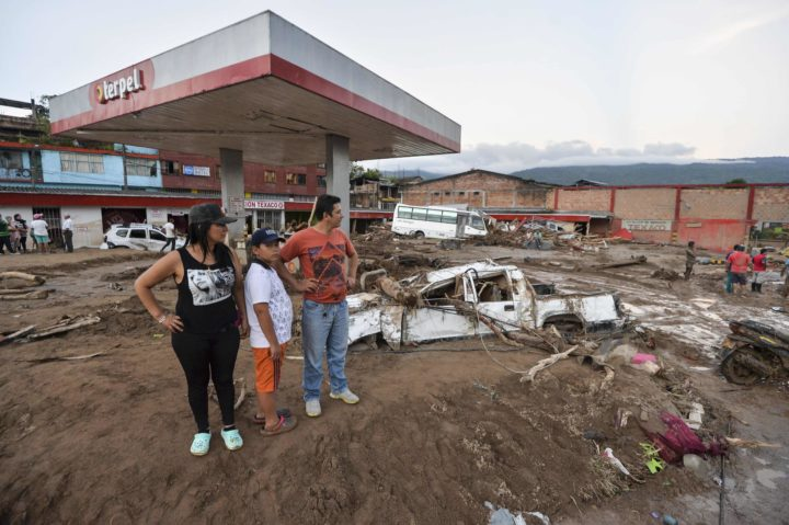 2017-04-01 18:16:06 People look at the damage caused by mudslides following heavy rains in Mocoa, Putumayo department, southern Colombia on April 1, 2017. A massive avalanche left more than 200 dead and hundreds of injured and disappeared on Saturday in southern Colombia, after heavy rains that have affected the Andean region, especially Peru and Ecuador. / AFP PHOTO / LUIS ROBAYO
