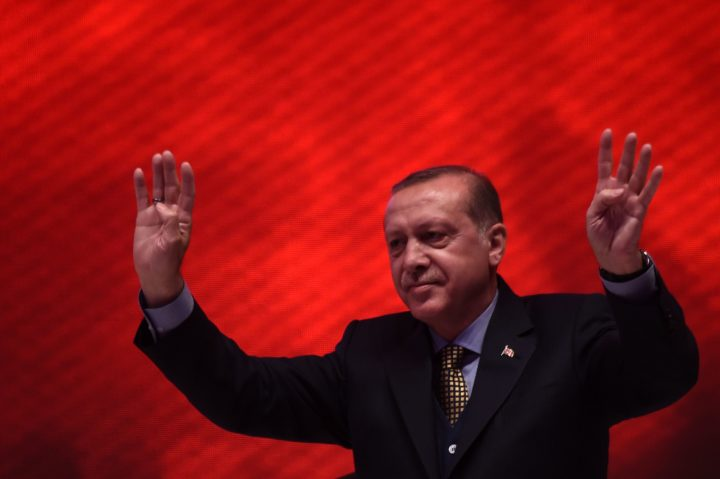 """2017-04-12 21:27:28 Turkish President Recep Tayyip Erdogan flashes the four-finger """"rabia sign"""" on April 12, 2017 during a 15 July Martyrs meeting and a campaign rally for the """"yes"""" vote in a constitutional referendum in Istanbul. Turks will vote on April 16, 2017 on whether to change the current parliamentary system into an executive presidency. / AFP PHOTO / OZAN KOSE"""