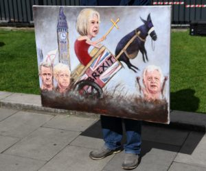 2017-06-09 08:25:57 TOPSHOT - Political artist Kaya Mar holds a painting depicting the faces of British Prime Minister Theresa May, British Foreign Secretary Boris Johnson, Britain's Secretary of State for Exiting the European Union (Brexit Minister) David Davis and Britain'sInternational Trade Secretary Liam Fox, as he stands on College Green, opposite the Houses of Parliament in central London on June 9, 2017 as results from a snap general election show the Conservatives have lost their majority. British Prime Minister Theresa May faced pressure to resign on June 9 after losing her parliamentary majority, plunging the country into uncertainty as Brexit talks loom. The pound fell sharply amid fears the Conservative leader will be unable to form a government and could even be forced out of office after a troubled campaign overshadowed by two terror attacks. / AFP PHOTO / Paul ELLIS / RESTRICTED TO EDITORIAL USE - MANDATORY MENTION OF THE ARTIST UPON PUBLICATION - TO ILLUSTRATE THE EVENT AS SPECIFIED IN THE CAPTION