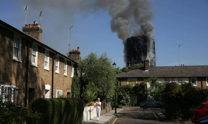 "2017-06-14 09:25:23 Local residents watch smoke billow from Grenfell Tower, a residential block on June 14, 2017 in west London. The massive fire ripped through the 27-storey apartment block in west London in the early hours of Wednesday, trapping residents inside as 200 firefighters battled the blaze. Police and fire services attempted to evacuate the concrete block and said ""a number of people are being treated for a range of injuries"", including at least two for smoke inhalation. / AFP PHOTO / Daniel LEAL-OLIVAS"