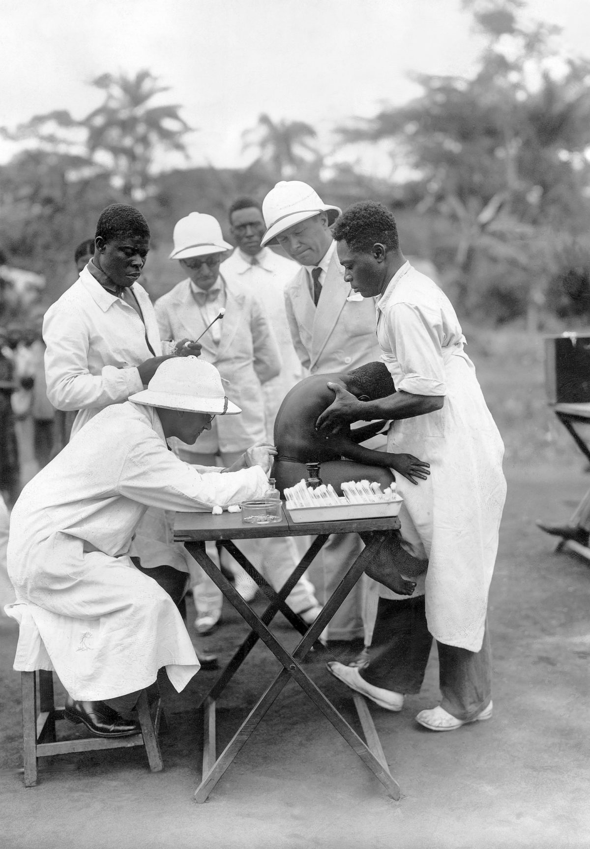 1933: French-Cameroon: European doctor inspects African boy for sleeping sickness and lumbar puncture.