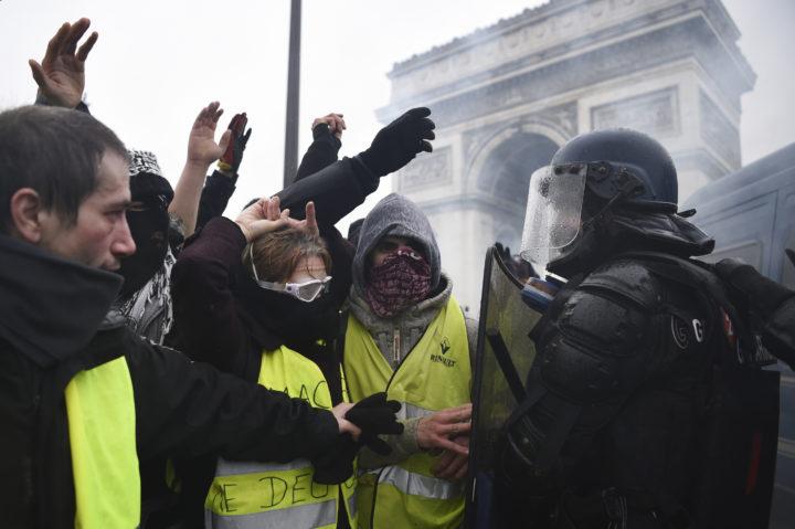 Gele hesjes tegenover de oproerpolitie in Parijs