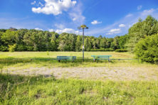 Takken en boomstammen op oud campingterrein tegen krakers
