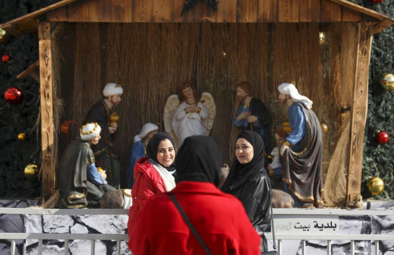 In Bethlehem kijken mensen naar een muurschildering van de geboorte van Jezus